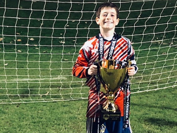 Young Boy stands in front of a goal with a trophy thanks to CHLA's help with this health