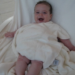 Baby lies on a chair with a happy face